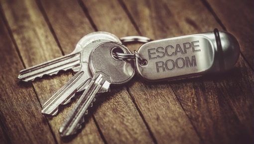 "3-4 keys on a wooden table coonected to the chain with the text ""escape room"""